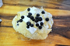 Fold and squish the dough until you have incorporated all the blueberries and cream cheese